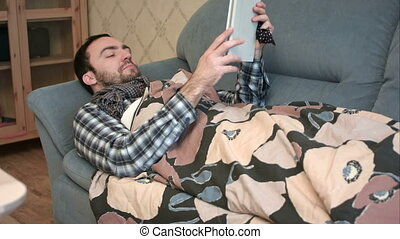 Sick young man using tablet computer lying on the sofa