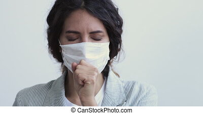Ill sick young woman having coronavirus pneumonia symptom short cough covers mouth wears medical face mask. Covid 19 virus infection spreading prevention, flu and cold treatment concept. Close up view