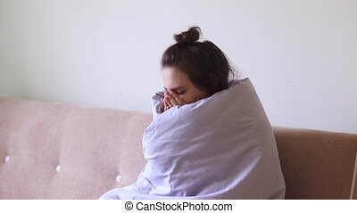 Sick young woman sits at home with a sore throat and coughs.