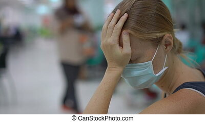 Sick young woman sitting in a hospital waiting for doctor's appointment