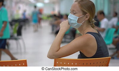 Sick young woman sitting in a hospital waiting for doctor's appointment.