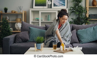Sick young woman taking body temperature with thermometer in house