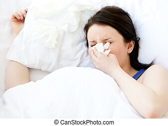 Sick young woman using a tissue lying in a bed at home