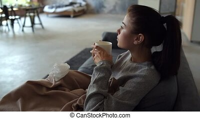 Sick young woman warming up with tea