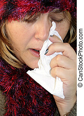 sickness - sick woman with a flu holding tissue