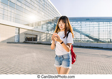 Side angle view of pretty 25-aged asian girl with long hair, wearing jeans and white t-shirt, using her smartphone while walking outdoors on the modern glass airport background