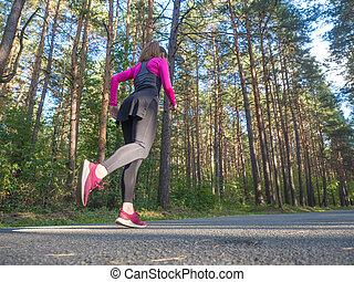 Side-back view of a running woman in wooded forest.