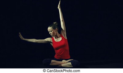 Side Bend - Woman doing side bends in seated pose in black...