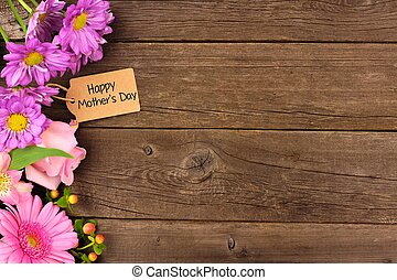 Side border of flowers with Mothers Day gift and tag against rustic wood