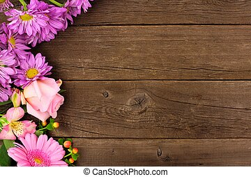 Side border of pink and purple flowers against a rustic wood background