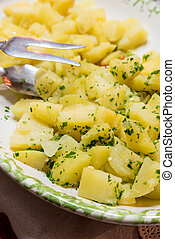 Side dish of boiled potatoes with parsley