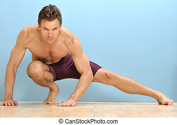 Muscular topless man performs side lunge stretch on wood floor and blue background