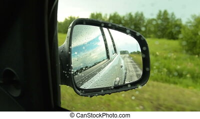 Side mirror view of car driving in the countryside on rainy day