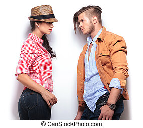 side of a young casual couple looking at each other