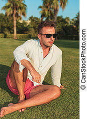 side of a young casual man sitting in the grass