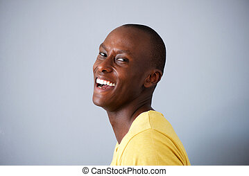 Side of handsome black man laughing against gray walll