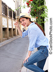 Side of happy woman leaning on wall outside with hand to hat