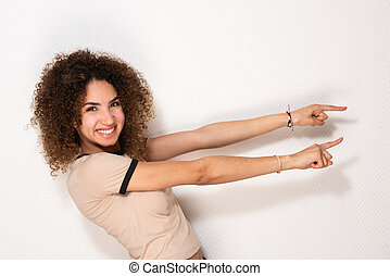 Side of happy young african american woman pointing fingers by white wall