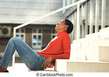 Side of happy young african American woman sitting on steps outside
