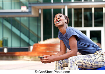 Side of happy young african american woman with cellphone outdoors