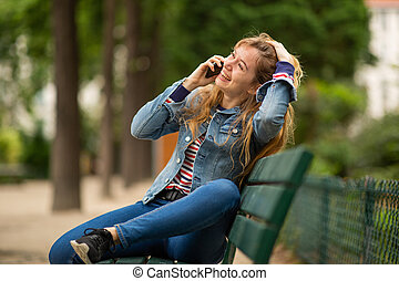 Side of happy young woman sitting on park bench talking with cellphone