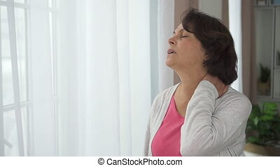 Side of mature woman massage neck standing on window background in home roome.