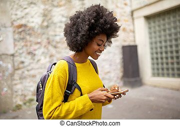 Side of smiling african american woman with bag and mobile phone walking in city