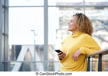 Side of smiling african american woman with cellphone
