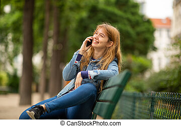Side of smiling young woman sitting on park bench talking with cellphone