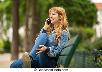 Side of smiling young woman sitting on park bench talking with mobile phone