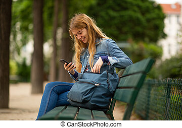 Side of smiling young woman sitting on park bench with mobile phone and bag