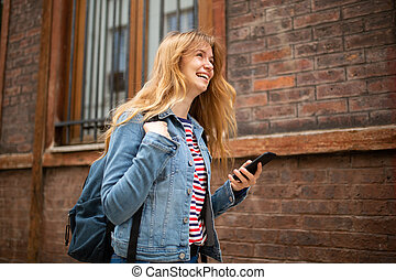 Side of smiling young woman walking with mobile phone and bag