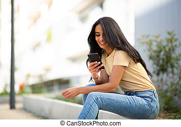 Side of young smiling woman sitting outside looking at mobile phone