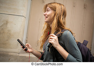Side of young woman smiling listening to music with earphones and cellphone
