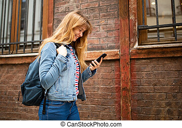 Side of young woman walking with mobile phone and bag