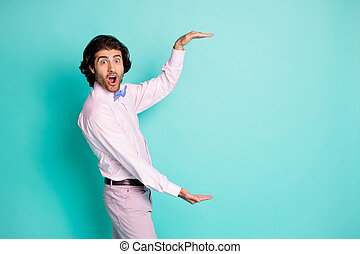 Side photo of cheerful brown wavy hair man wear pink outfit measure empty space two hands isolated teal color background