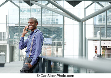 cool african businessman smiling with cellphone in building