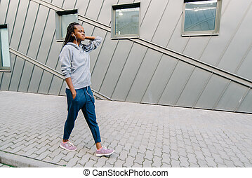 Side portrait of a smiling african american woman walking in the city with headphones