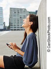 attractive young woman sitting outdoors with cell phone and laughing