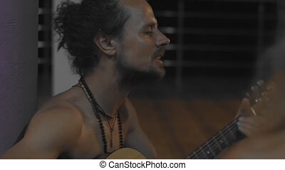 Side portrait of authentic hippie musician playing guitar sitting on street outdoors handheld device. Bearded man performing music outside in india slow motion. Real people lifestyle storytelling