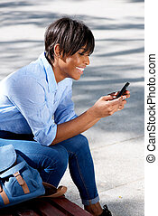 young african woman sitting on bench looking at text message on smart phone