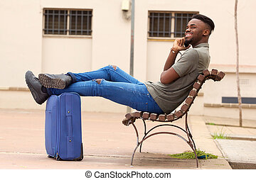 happy african american man sitting outside with suitcase and talking on cell phone