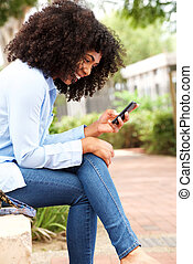 happy young african american woman sitting outdoors and using cell phone