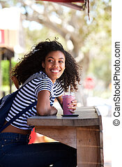 happy young african american woman sitting outdoors holding smoothy drink