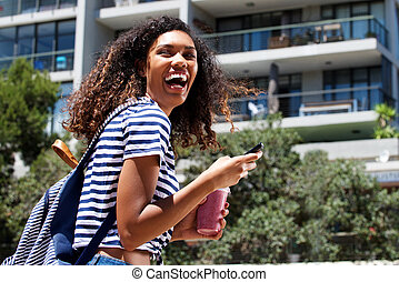 happy young african american woman walking outdoors with cellphone
