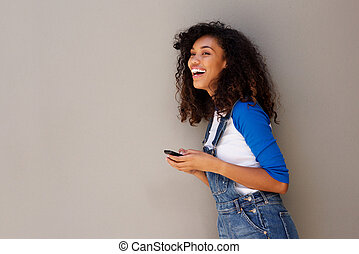 happy young african woman laughing with cellphone