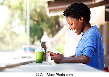 happy young african woman sitting at cafe using mobile phone