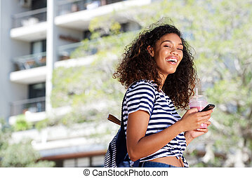 happy young african woman walking outdoors with cellphone