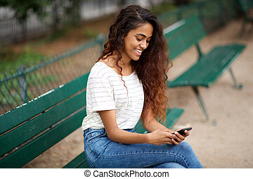 happy young indian woman sitting on bench in park with cellphone