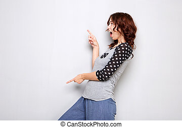 happy young woman pointing fingers at copy space on gray wall